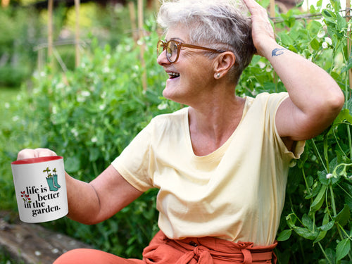 Cool older white woman sitting in a garden sipping from a Life is Better in the Garden mug from Ferry-Morse.