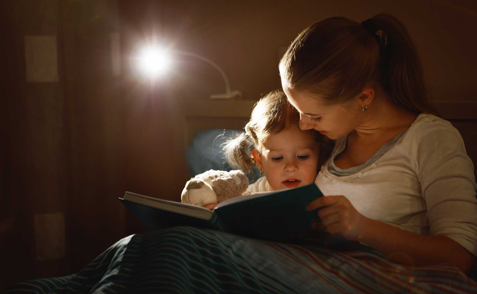 mom reading bedtime book to toddler
