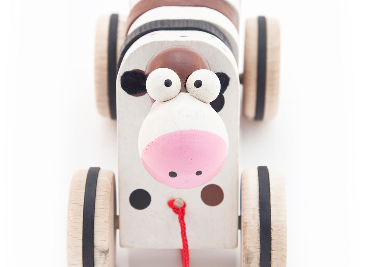 Cute wooden cow toy looking up, kids love her silly looks