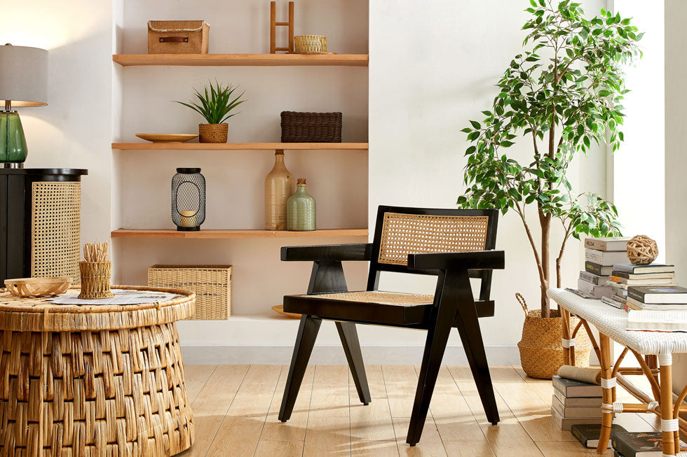 A black accent chair with natural rattan seat and back is set in a coastal theme room with natural decor.