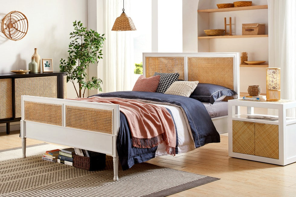 Wicker and white wood bed with matching furniture in a light and airy room.