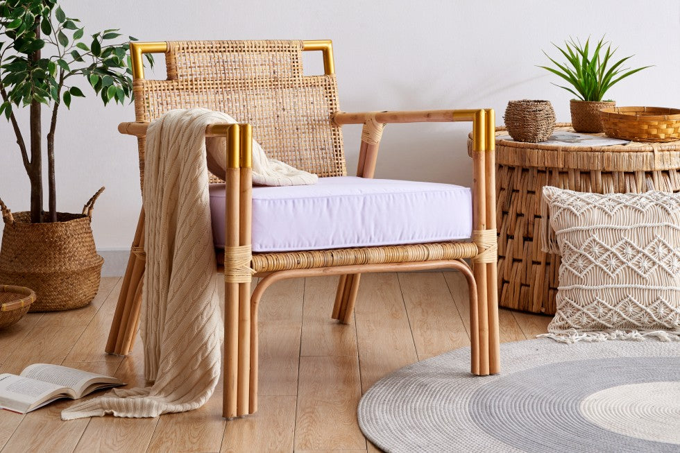 light and airy wicker chair with white cushion and beige throw. Set in a coastal themed room with macrame and potted plant decor.