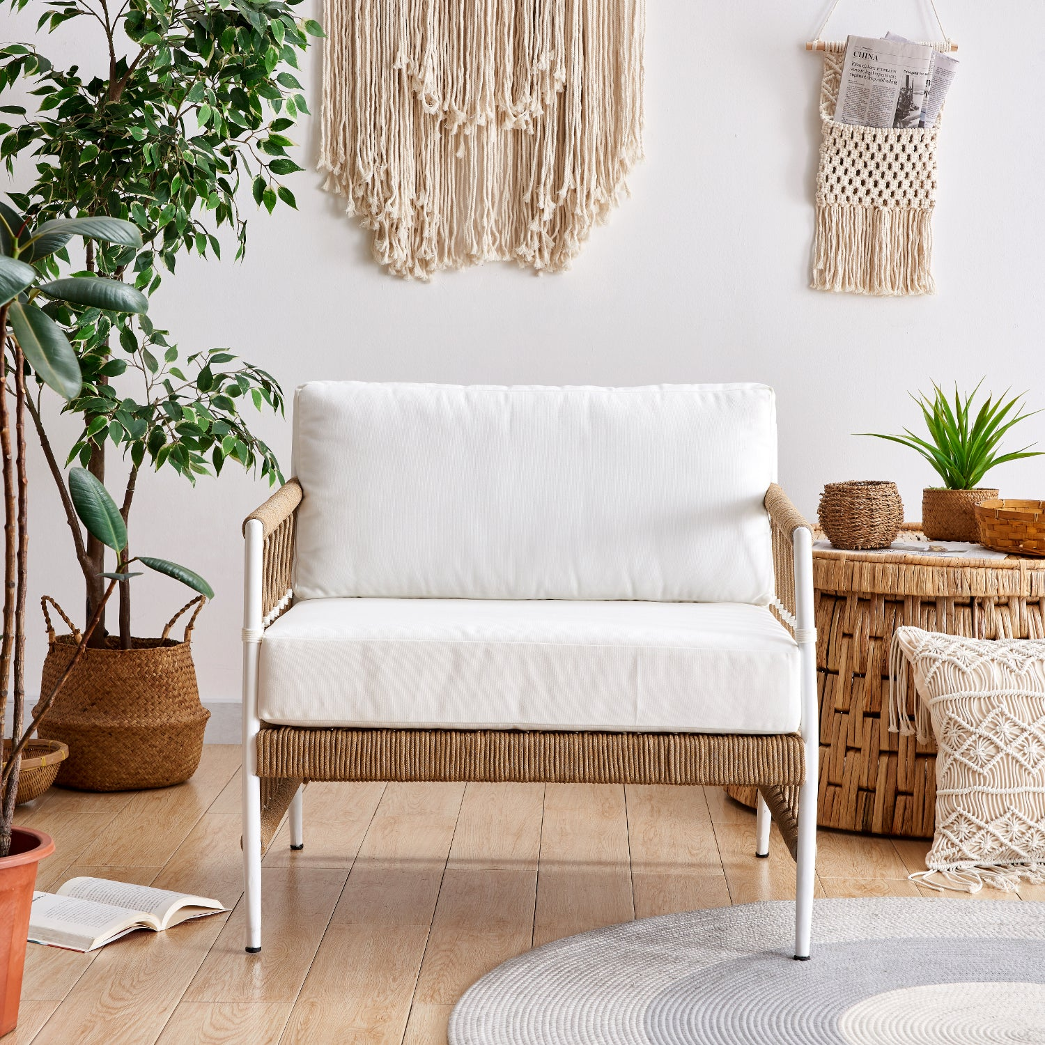 light wicker sofa styled with bolster pillows, soft throw blanket, and macrame decor. Set in an earthy room with natural fiber decor and hardwood floors.