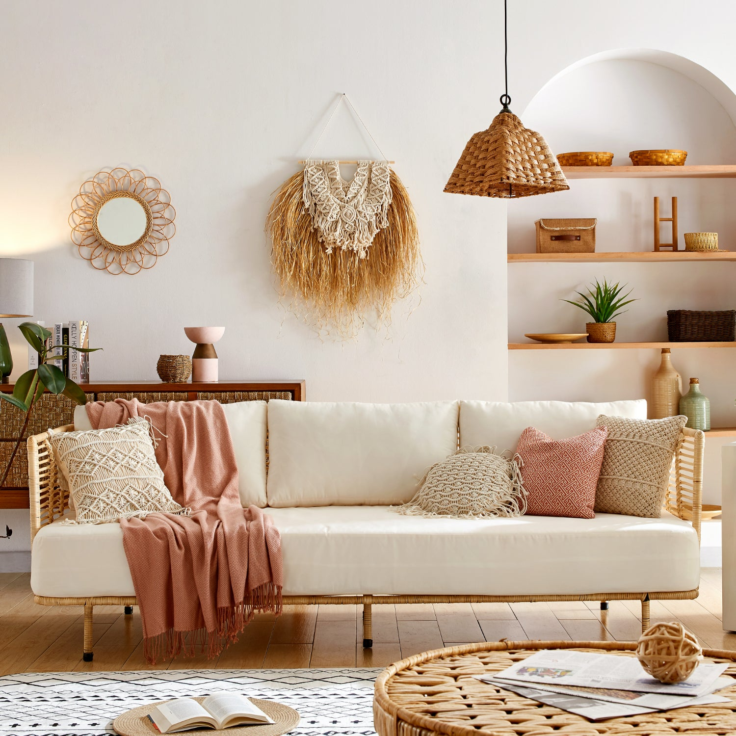 Plush white cushion sofa with wicker frame in a coastal decor room. Decorated with plants and natural fubar decor.