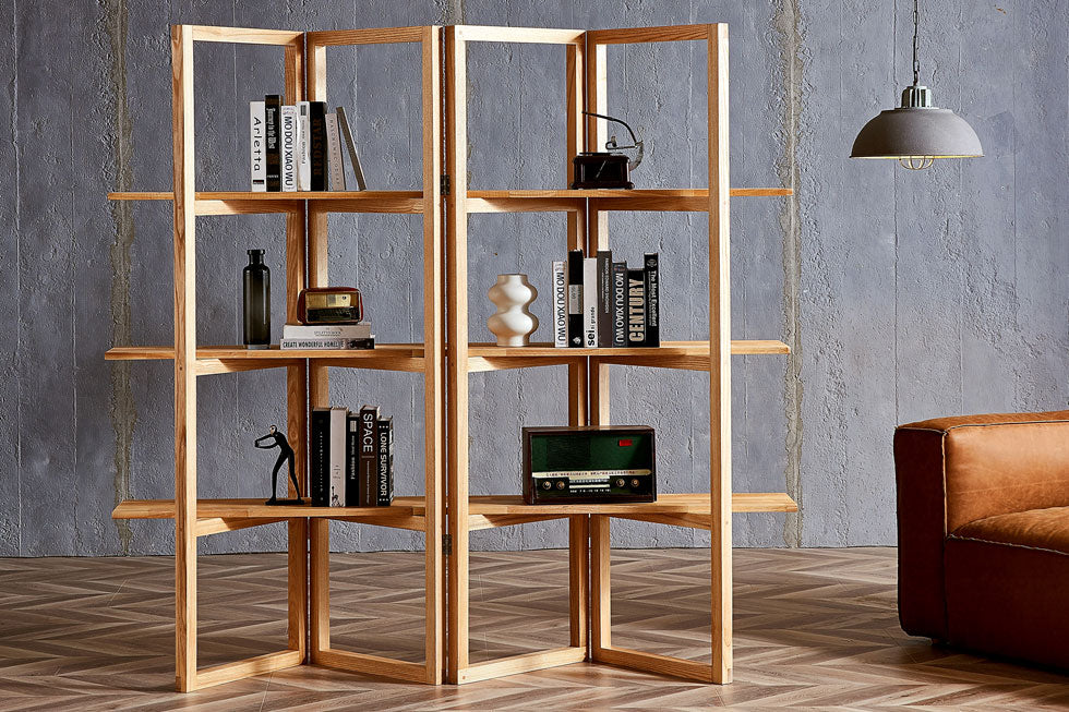 An open shelf wood bookcase styled with books and vintage decor is set in an industrial style room with concrete wall.