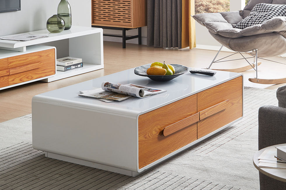 Large coffee table with storage. sleek, white with tempered glass top and sides, wood drawers, and a smooth, rounded, minimalist design.