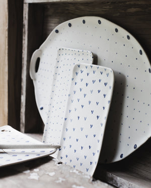 Selection of rectangular ceramic plates and large platter with handles decorated in blue and white spots diamonds and hearts by clay beehive.