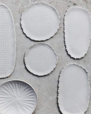 A selection of satin white plates with textured rim and surfaces
