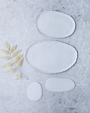 A collection of oval shaped fabric textured plates