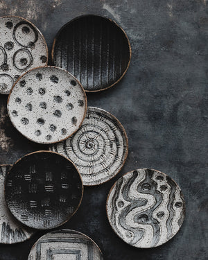 hand made ceramic rustic tapas sharing plates with carved designs glazed in satin black and white by clay beehive