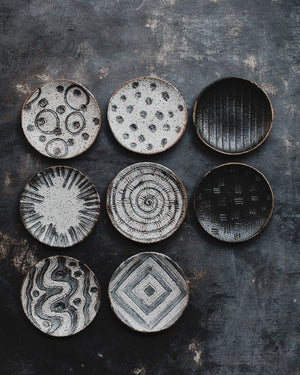 hand made ceramic rustic gritty tapas sharing plates with carved designs glazed in satin black and white by clay beehive