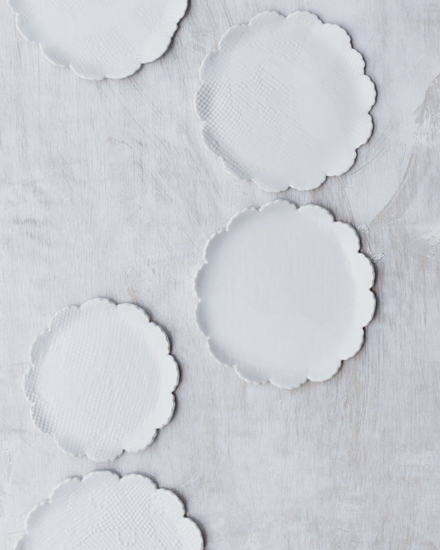 satin white hand made ceramic plates with petal curved rims by clay beehive