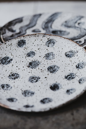 close up view of hand made ceramic rustic gritty tapas sharing plates with carved designs glazed in satin black and white by clay beehive
