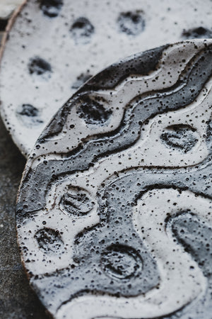 macro view of hand made ceramic rustic gritty tapas sharing plates with carved designs glazed in satin black and white by clay beehive