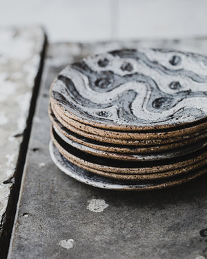 stack of hand made ceramic rustic gritty tapas sharing plates with carved designs glazed in satin black and white by clay beehive