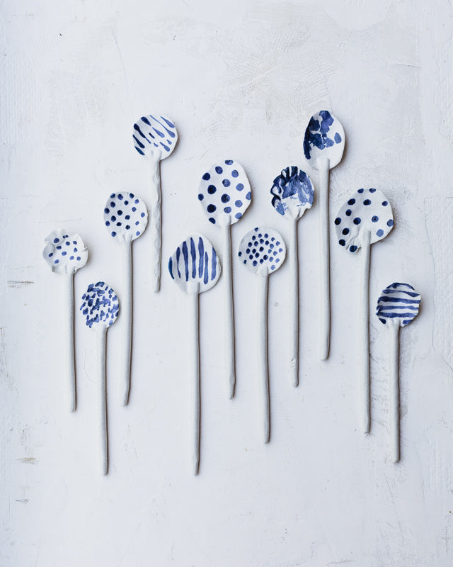 hand made ceramic spoons decorated in blue and white spots and stripes by clay beehive