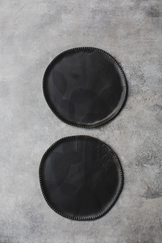 black ceramic plates with textured rims handmade by clay beehive
