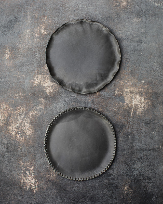 Satin black plates with textured rims made by clay beehive ceramics