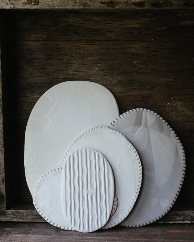 satin white flat plates with textures hand crafted by clay beehive ceramics