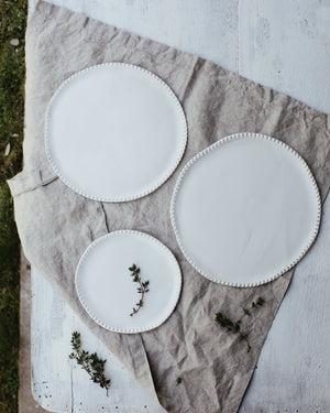 satin white plates with textured rims hand crafted by clay beehive