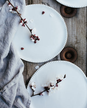 satin white ceramic plates with textured rims hand crafted by clay beehive