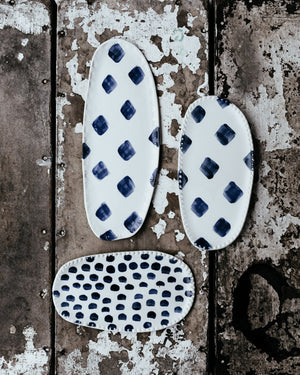 Small oval handmade ceramic plates in blue and white by clay beehive