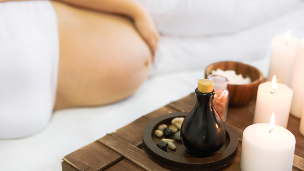 Pregnant woman lying on a massage table next to massage oil and candles
