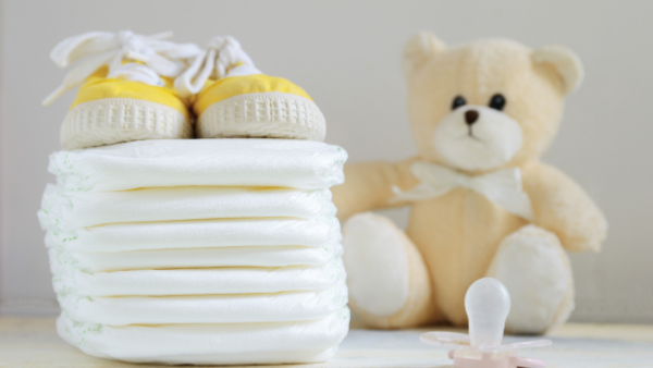 a stack of white nappies with yellow shoes on top, sitting next to a teddy bear