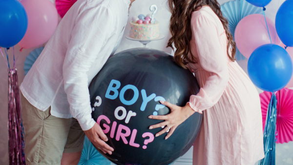 pregnant woman kissing her partner whilst holding a balloon that will reveal the baby's gender