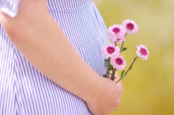 Closeup of pregnant woman's belly as she holds flowers near her baby bump - BabyHeart Australia