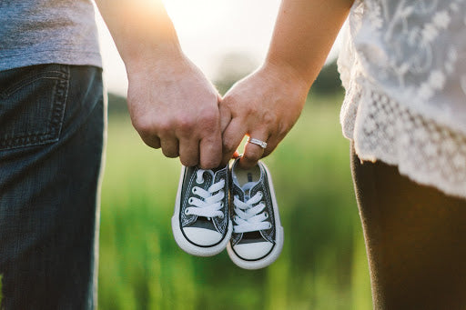 New parents expecting a baby - pregnant couple holding baby shoes