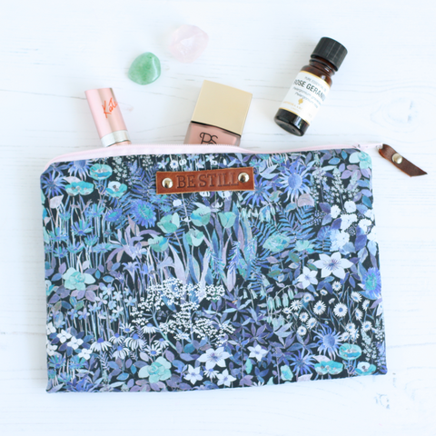 Floral fabric makeup bag with 'Be Still' embossed tag