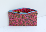 Pink floral fabric makeup bag with 'Equality' embossed tag