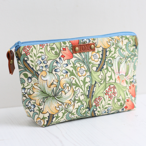 Green floral makeup bag with 'JOY' tag