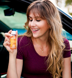 woman holding vitamin c shot