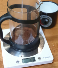 pouring water over freshly ground coffee in a cafetiere