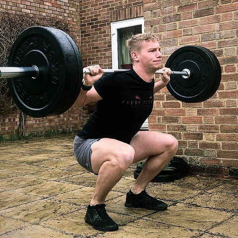 Man squatting with Olympic weights on patio
