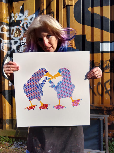 Liz holding screen print of two blue footed boobies dancing