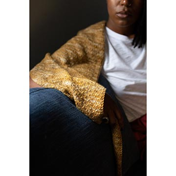 woman sitting on a couch wearing Fino shawl