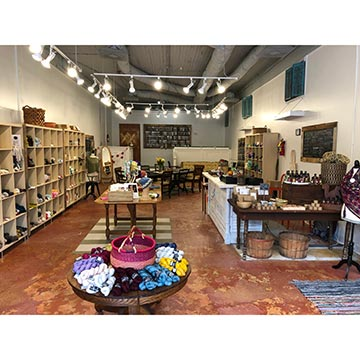 Image of The Craftivist yarn store with lots of yarn on tables