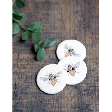 Image of ceramic bee buttons on wood table