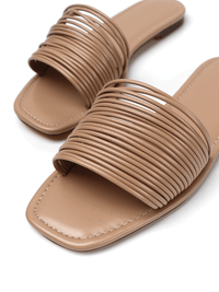 Close up of straps on nude flat sandals slides