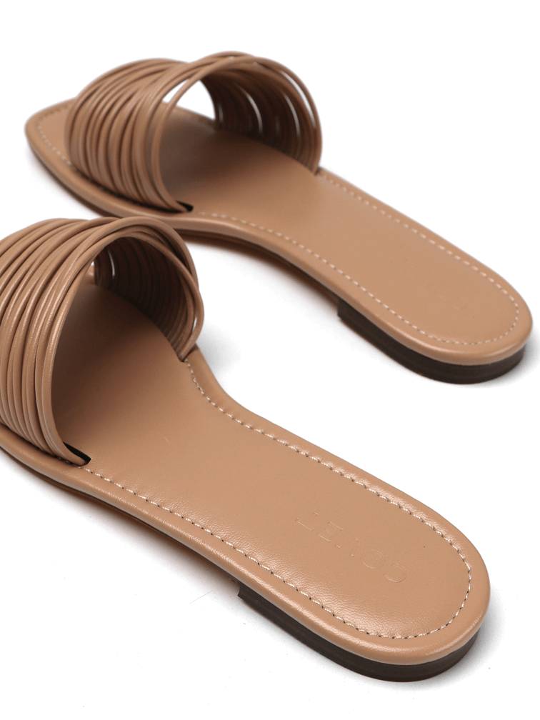 Heel details of pair of strappy nude flat slides sandals