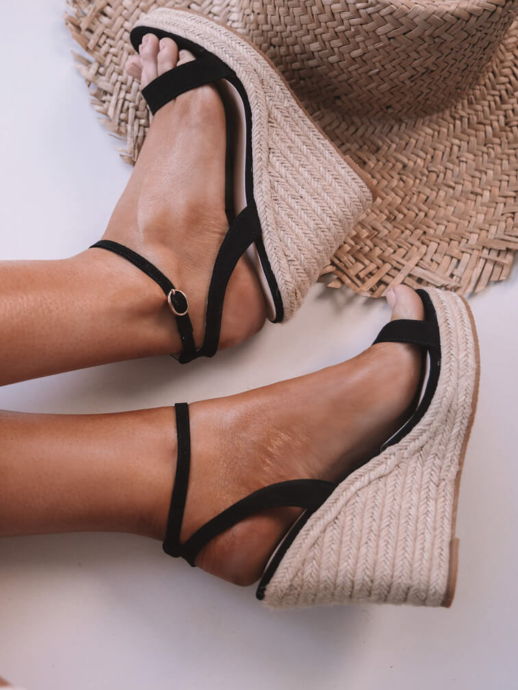 Side view of Black Wedges on women's foot