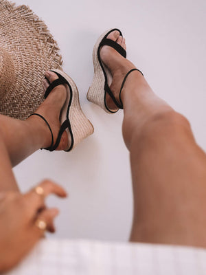 Black wedges on a womens foot from her perspective