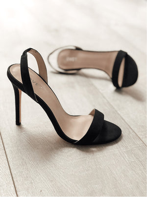 Pair of black slingback heels with one heel in the forefront and one heel in the background