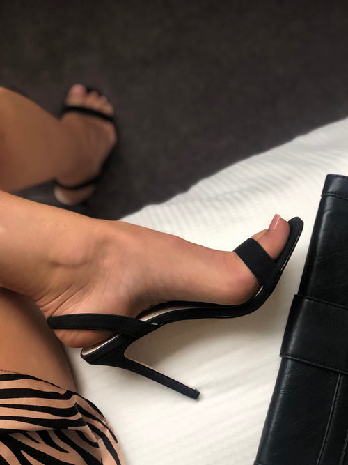 Black slingbacks on women's foot getting dressed for a night out