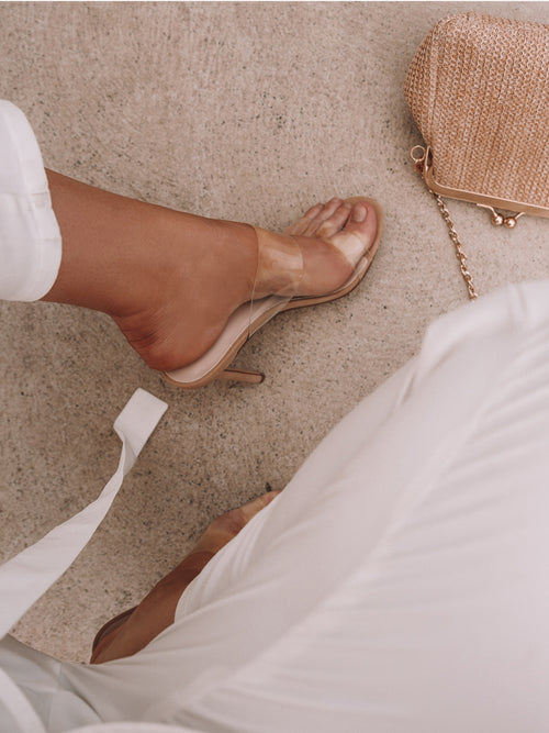Women wearing nude stilettos mule style with two clear straps at the font