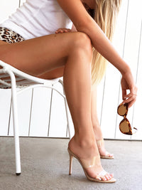 Woman sitting on a chair wearing 10cm nude heels with a stiletto style heel with sunglasses in her hand