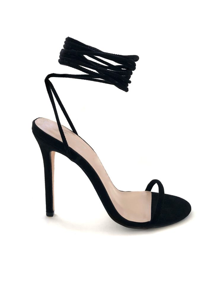 Side profile of lace up black stiletto heels with a tubular strap at the front